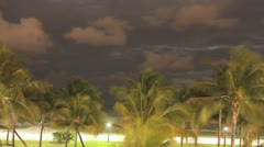 Time lapse Night Clouds roll over the Miami palm trees and the ocean Stock Footage