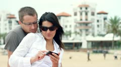Happy couple with cellphone, outdoors HD - stock footage