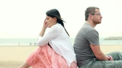 Relationship difficulties, young couple sitting by the beach HD Stock Footage