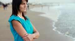 Sad pensive woman standing on the beach, steadicam shot HD - stock footage