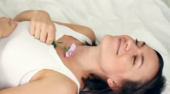 Happy young woman lying in bed and smelling flower - stock footage