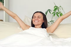 Young attractive woman stretching and yawning in bed - stock footage