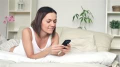 Happy woman in bed sending sms, text message, dolly shot Stock Footage