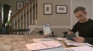 Stock Video Footage of A man going over his bills on his dining room table (1 of 3)