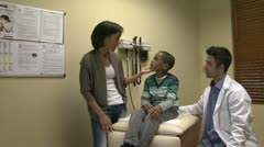 Concerned mom with her son at doctors office - stock footage