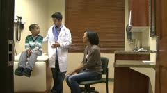 Doctor talks with mom and son - stock footage