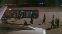Transfer coach dropping off passengers to board aeroplane Stock Footage