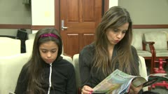 Mother and daughter in waiting room at doctor's office Stock Footage