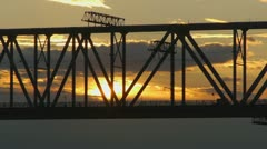 Freight train rides on the railway bridge at sunset Stock Footage