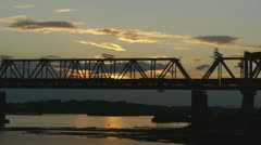Train rides on the railway bridge at sunset Stock Footage