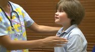 Nurse checks young child's glands Stock Footage