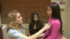 Girl has her lungs checked by nurse - stock footage