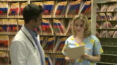 Doctor and Nurse discuss patient's chart (1 of 3) Stock Footage