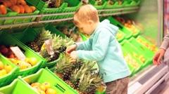 Boy choosing pineapple - stock footage