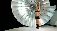 Young girl make active movements by her legs, in photo studio Stock Footage