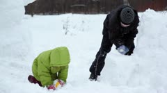Brother and sister play with snow in park at winter Stock Footage