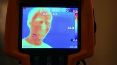 Hand hold thermal image camera, on-screen human face, hand, man opens mouth Stock Footage