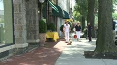 Woman with dog on leash on sidewalk Stock Footage