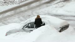 Woman digs out car littered with snow Stock Footage