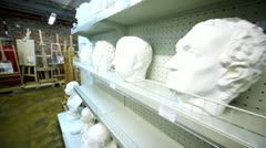 Several sculpture heads are on shelves in store Stock Footage