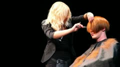 Hairdresser Eugenia Soboleva makes hairstyle for man at Davines Hair Show 2010 Stock Footage