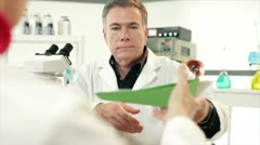 Scientist giving paperwork to a tech Stock Footage