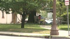 Woman sitting on bench along sidewalk Stock Footage