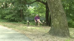 Man sitting on bench in park Stock Footage