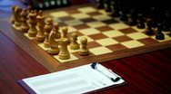 Hand arranges figures on chessboard, paper for log moves lay on table Stock Footage