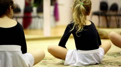 Little girls sit on floor and streches risen legs, view from behind Stock Footage