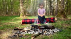 Little girl sits on log and watch at bonfire burn Stock Footage