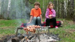Boy and little girl sit on log, fresh meat cooking on embers Stock Footage