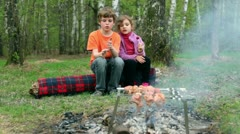 Boy and little girl sit on log, bot hold empty glass and girl eat candy - stock footage
