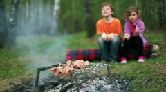 Boy and little girl sit on log and watch at fresh meat on embers Stock Footage