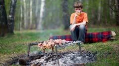 Boy sit on log and drink juice, meat cooking on embers Stock Footage