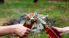 Two hands clink bottles with beer, at background of kebab on bonfire Stock Footage