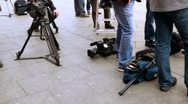Television equipment lay on ground near operators legs Stock Footage