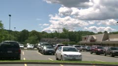 Looking over parked cars in parking lot in small plaza Stock Footage