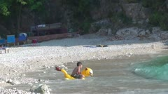 A child on a rubber toy entering the sea Stock Footage