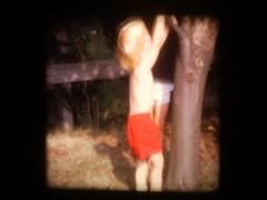 2 little boys hang on tree Stock Footage