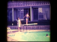 Skinny Pre-teen boy dives into hotel swimming pool Stock Footage