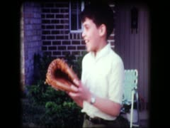 Cute young boy tossing baseball glove - stock footage