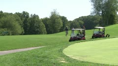 Two golf carts with golfers waiting to putt - stock footage