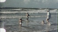 Stock Video Footage of Family Runs into Beach Waves Circa 1960 (Vintage Film Home Movie) 1908