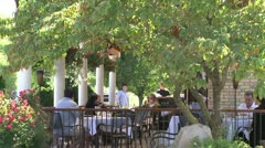 People dining on a patio outside a restaurant Stock Footage