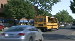 School bus moving with local traffic Stock Footage