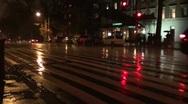 Pedestrians in rain cross street at crosswalk, night. Stock Footage