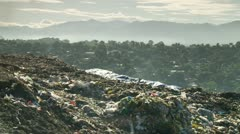 Trash pickers collect garbage in an open dump site Stock Footage