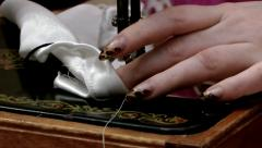 Dexterous hands and fingers of the dressmaker easily cope with threads Stock Footage