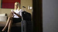 Female manager using mobile phone in hotel room during business trip Stock Footage